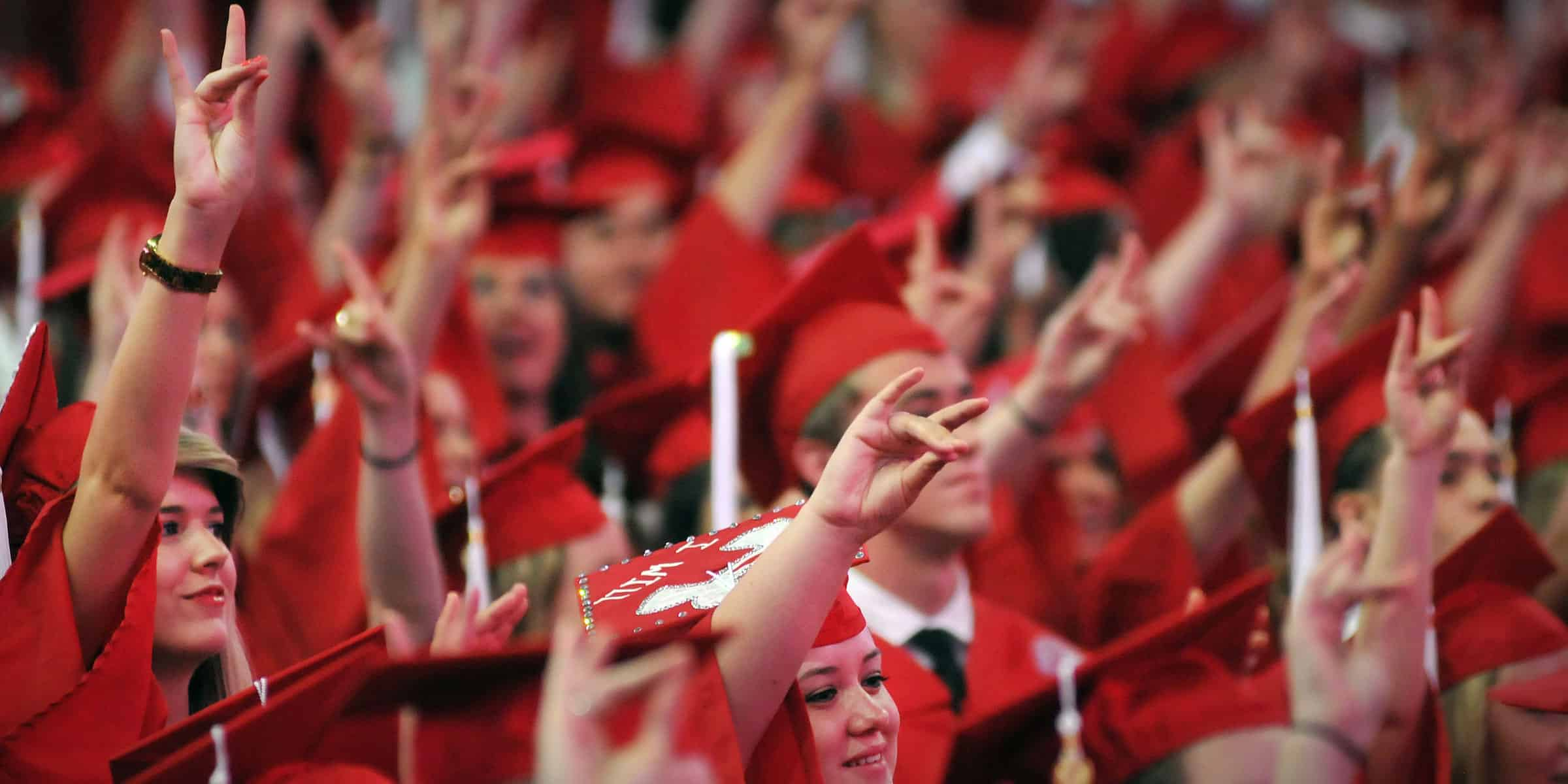Students hold up wolf hand at graduation ceremony